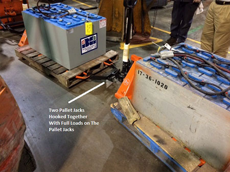 two pallet jacks hooked together with loads